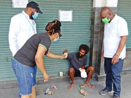 Councillor for the Lime Hall division in St Ann, Genevor Gordon-Bailey, offers a cup of juice to one of the street persons in Ocho Rios, who was involved in a conversation with Mayor Syndey Stewart (right) and former mayor and councillor for the Ocho Rios