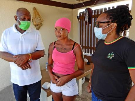 Simone Williams (centre) shares some of her experiences while living on the streets with Mayor Sydney Stewart (left) and Councillor Genevor Gordon-Bailey, on Good Friday. Williams is one of approximately 70 persons the St Ann Municipal Corporation targeted