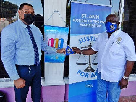 Rotary Club of Ocho Rios' newest member, Paolo Fakhourie (left), collects a mask from Pixley Irons, JP and president of the Rotary Club, at the start of the mask distribution initiative in Ocho Rios.