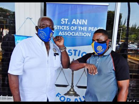 Rodney Campbell (right), shows his appreciation at getting a mask by touching elbows with Pixley Irons, JP and president of the Rotary Club of Ocho Rios.