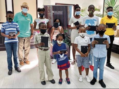 Pierre Battaglia, general manager of Couples Sans Souci, with some of the children of staff who received tablets during a presentation at the hotel recently.