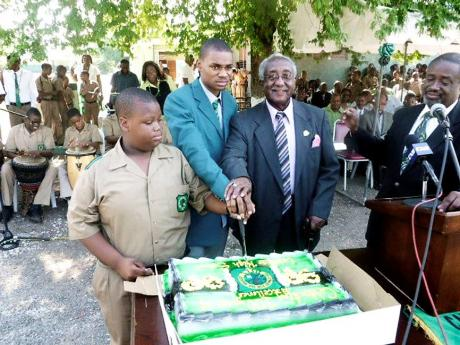The Rev Dr Horace Russell cuts a cake alongside Olympian Warren Weir (centre) at Calabar High School while the Rev Dr Karl Johnson, general secretary of the Jamaica Baptist Union, looks on. Russell died on Monday aged 91.