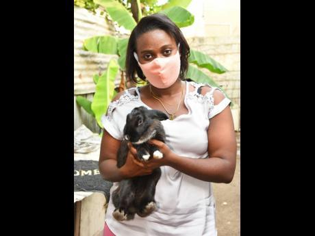 Inner-city entrepreneur, Gewana Reid, with one of the rabbits she rears and sells in Denham Town, Kingston.