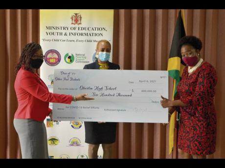 Fayval Williams (centre), minister of education, youth and information, and Nola Wright (left), member of the Oberlin High School Class of 1989 alumni, presents a cheque valued at $600,000 to Michelle Spencer, principal of Oberlin High School. The donation