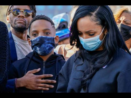 One of DMX's sons (centre) is joined by friends and family members during a prayer vigil for the rapper outside of White Plains Hospital on Monday.