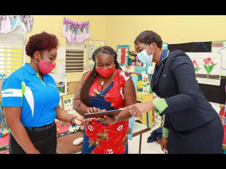 Sharon Byfield (centre), principal of the Clifton Basic School in Portmore, St Catherine, tests out one of the tablets she received from members of the Outreach Committee at the Sagicor Bank Portmore branch (from left) Janet Grey, assistant branch manager,