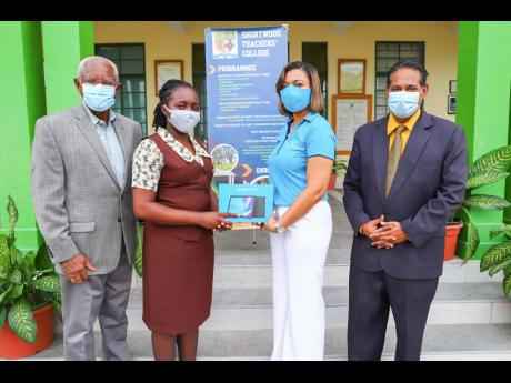 Marie Dowdie (second right), assistant branch manager, Sagicor Bank Manor Park location, presents a tablet to Jon-Benet Brown (second left), final-year student and vice-president of the Student Council body at the Shortwood Teachers' College, at the scho