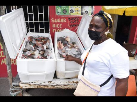 Maureen 'Angella' McDermott, a vendor who operates at the Rae Town fishing village in Kingston, shows a fresh supply of fish she has for sale. She lamented having lost thousands of dollars from rotting fish on the Easter lockdown weekend.
