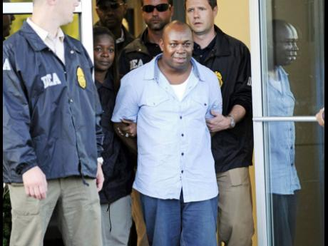 Christopher 'Dudus' Coke is led away by law-enforcement officials at Westchester County Airport in New York in 2010.