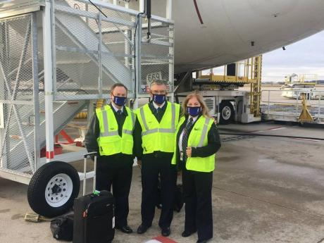 From left: FedEx Captains Trey Hollingsworth, Tom Gregory  and Muriel Zarlingo (right) share lens time on the tarmac in Grand Rapid, Michigan, where they went to pick up the first shipment of COVID-19 vaccines to be delivered in the United States late last