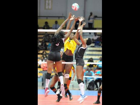 Trinidad and Tobago's Sinead Jack (left) and Renele Forde (right) go up to attempt a block on Jamaica's Danaisha Moss, during the 2017 Caribbean Volleyball Championships at the National Indoor Centre in Jamaica.