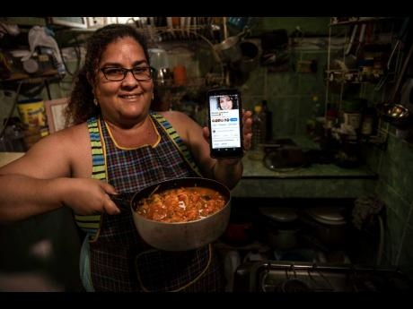 Contributor Yuliet Colon poses for a photo holding a pot of her creation, 'Cuban-style pisto manchego',  and her phone that displays the Facebook page, 'Recipes from the Heart', in her home in Havana, Cuba, on Friday, April 2.