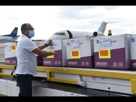 Minister of Health and Wellness Dr Christopher Tufton accepting a shipment of 75,000 doses of AstraZeneca COVID-19 vaccines shortly after it arrived at the Norman Manley International Airport in Kingston via a chartered flight from Ghana on Thursday, April