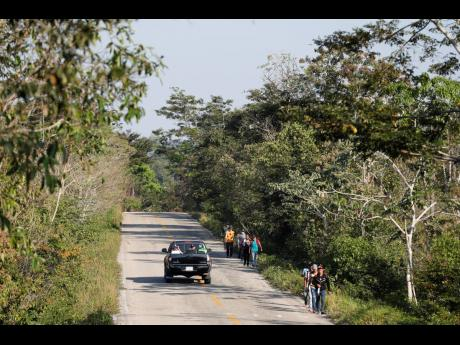Migrants trek on the highway from Frontera Corozal to Palenque, Chiapas state, Mexico, on Wednesday, March 24, 2021.