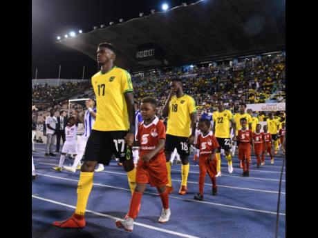 Damion Lowe (left) leads the Reggae Boyz on to the field at the National Stadium in 2019 to take on Honduras in a Concacaf Gold Cup match.