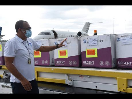 Ian Allen Minister of Health and Welness Dr. Christopher Tufton looks at the 75,000 doses of AstraZeneca vaccines shortly after it arrived in the island via a chartered flight from Ghana on Thursday.