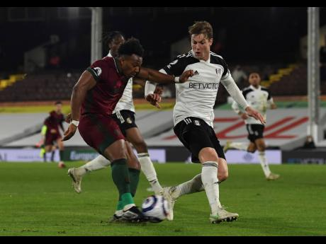 Wolverhampton Wanderers' Adama Traore (left) scores the opening goal during their English Premier League match against Fulham at Craven Cottage in London, England on Friday.