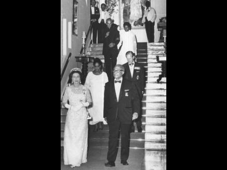 Her Majesty the Queen and Governor General Sir Florizel Glasspole descend the main stairway from the drawing room to the ballroom at King's House for the state dinner, followed by Lady Glasspole and Prince Philip, then Prime Minister Michael Manley and B