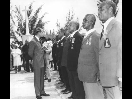 Prince Philip pauses to chat with some of the war veterans who attended the wreath-laying ceremony at the National Heroes Park on April 29, 1975.