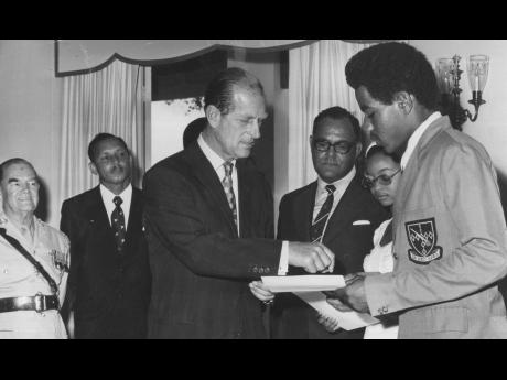 Prince Philip presenting the Gold Award Certificate for participation in the Duke of Edinburgh Award Scheme to Jamaican Errald Jordine on April 30, 1975. Second from right is Claire Shackleford from The Bahamas, who also received her certificate at King'