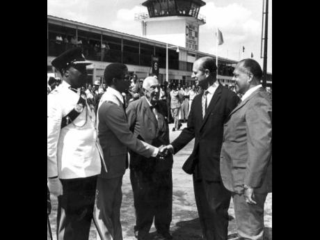 Prince Philip (right) is introduced to the Mayor of Montego Bay Charles Sinclair (second left) by St James Custos Walter Fletcher on the Duke's arrival at the Sangster International Airport in May 1975 for a tour of the Cornwall Regional Hospital.