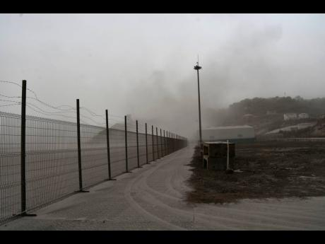 A road is blanketed in volcanic ash at the international airport in Kingstown, on the eastern Caribbean island of St Vincent, on Saturday, April 10, 2021 due to the eruption of La Soufriere volcano.