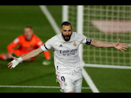 Real Madrid's Karim Benzema celebrates after scoring the opening goal past Barcelona's goalkeeper Marc-Andre ter Stegen (background) during the Spanish LaLiga match between Real Madrid and FC Barcelona at the Alfredo di Stefano stadium in Madrid, Spain, ye