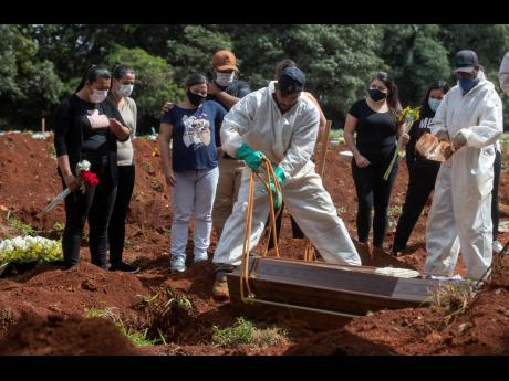 People attend the burial of a relative who died from complications related to COVID-19 at the Vila Formosa cemetery in São Paulo, Brazil, Wednesday, April 7.