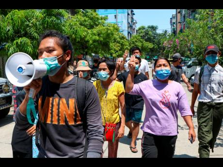 Young demonstrators flash the three-fingered symbol of resistance as they march in Yangon, Myanmar, Saturday, April 10. Security forces in Myanmar cracked down heavily again on anti-coup protesters Friday even as the military downplayed reports of state vi