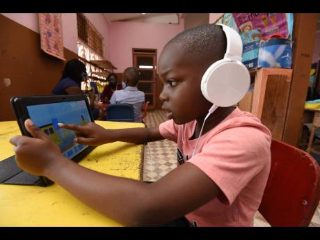 Seven-year-old Joachim Walker works on his tablet computer. A student of Kitson Town Primary School in St Catherine was one of the recipients of the tablet computers.