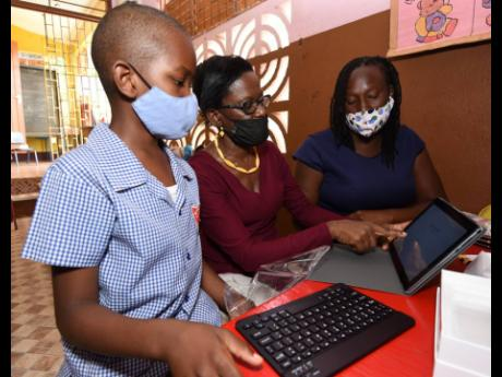 Pearline Gordon (centre), a teacher at the Kitson Town Primary School, with her student Daniel Edwards (left) and his mother Jovian Edwards (right) shortly after Daniel was presented with a tablet computer.