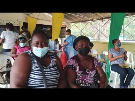 Aneika James and her 67-year-old mother Novlette James celebrate receiving the first dose of the COVID-19 vaccine during the blitz held Saturday at the Denbigh Agricultural Showground in May Pen, Clarendon.