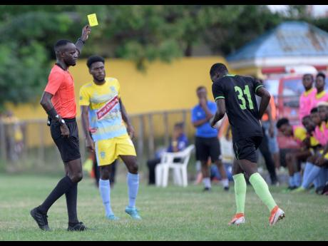 Referee Oshane Nation (left) shows Molynes United defender Fakibi Farquharson (right) a yellow card moments after he committed a foul on a Waterhouse player during a Jamaica Premier League match at the Constant Spring Sports Complex on Sunday, November 3,