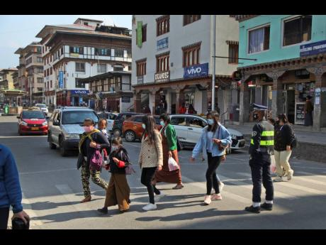 Bhutanese people wearing face masks as precaution against coronavirus cross a street in Thimpu, Bhutan, yesterday. The tiny Himalayan kingdom, wedged between India and China, has vaccinated nearly 93 per cent of its adult population since March 27. Overall