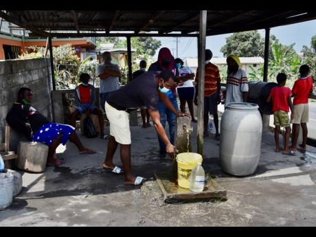 People collect water not contaminated by volcanic ash after the eruption of La Soufriere volcano in Wallilabou, on the western side of the Caribbean island of St Vincent, Monday, April 12, 2021.
