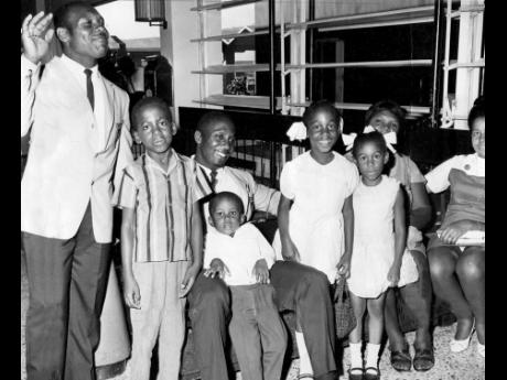 Weightlifter Cedric Demetrius (left) and fellow weightlifter Keith Bailey (sitting third from left) pose with members of their families ahead of their departure to the 1968 Olympic Games in Mexico City, Mexico.