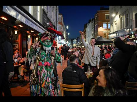 People sit at set-up tables outside pubs in Soho, in London, on the day some of England's third coronavirus lockdown restrictions were eased by the British government on Monday. Pubs, shops and hairdressers have opened as lockdown restrictions are eased