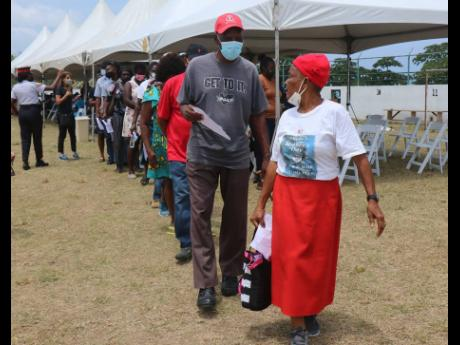 Persons waiting in a line to get vaccinated against COVID-19 at the Hopewell Sports & Community Centre in Hanover.