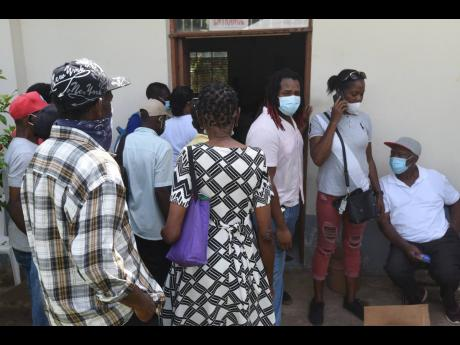 Frustrated persons gather at the door to the vaccination centre at the Holy Trinity Anglican Church in Linstead, St Catherine, on Tuesday when they heard that they would not be immunised until next week Tuesday. When new vials arrived, persons were told th