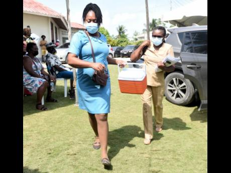 A healthcare worker rushes with an igloo with 200 vaccines after public health nurse Novelette Stennett arrives at the Holy Trinity Anglican Church in Linstead, St Catherine, on Tuesday. The centre ran out of vaccines early in the morning, with some person
