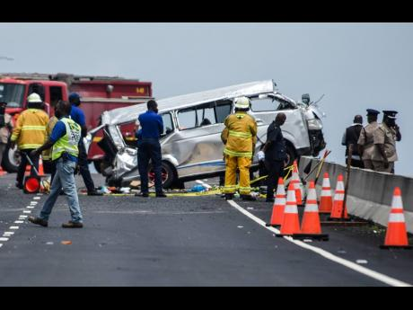 Firefighters and police are observed at the scene of a traffic crash on Highway 2000 on Monday. Five people died from their injuries.