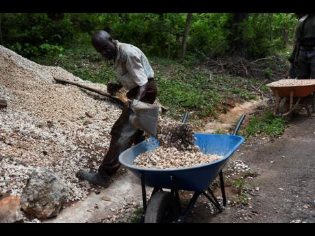Orville Franklyn, seen here shovelling gravel in Mendez, St Catherine, in helping his older brother build his home. Franklyn has called for lockdown grants to be issued to hard-hit Jamaicans.