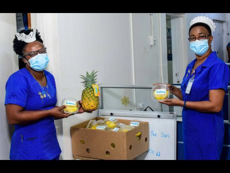 Annotto Bay Hospital Deputy Matron Tracey Ann Reynolds (left) and Matron Claudia McLennon choose from a selection of freshly peeled JP St Mary's pineapples, delivered fresh from the farm last month. The sweet treats were delivered to the healthcare worke