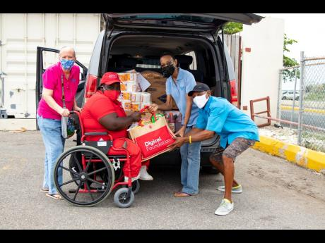 Representatives of the STEP Centre for Children with Multiple Disabilities, Hillary Sherlock (left), Dana Oldfield-Williams (second right) and Ronald Seivwright (right) are presented with donations to support their students and families by Digicel Foundati