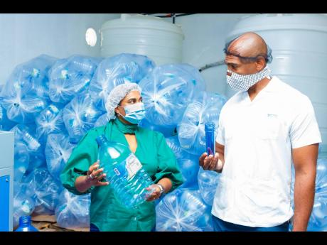 Dr Alfred Dawes observes the recycling and packaging capabilities at Lifespan Spring Water Ltd's Buff Bay Portland facility along with Company CEO Nayana Williams.