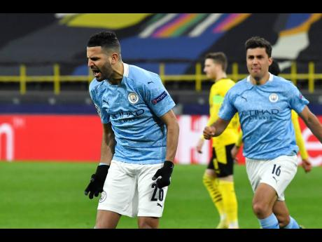 Manchester City's Riyad Mahrez (left) celebrates after scoring his side's first goal during the Champions League quarter-final second leg match between Borussia Dortmund and Manchester City at the Signal Iduna Park stadium in Dortmund, Germany, yesterd