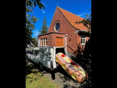 This photo provided by Ross Hall shows a cream doughnut-shaped coffin for the funeral of Phil McLean outside a church in Tauranga, New Zealand, on Feb 17. Auckland company Dying Art makes unique custom caskets which reflect the people who will eventually l