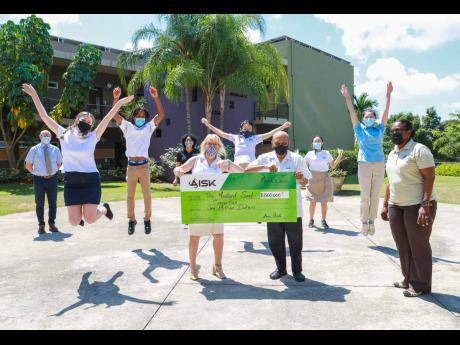 Students jump for joy as the cheque is handed over by Susan Canobie, head of school, American International School of Kingston to Monsignor Gregory Ramkisson. Darcy Tulloch-Williams, executive director, Mustard Seed Communities, looks on. Back, from left: