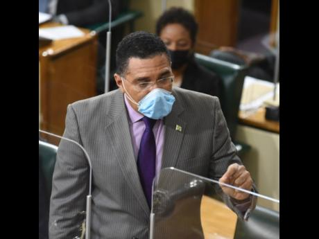 A masked Prime Minister Andrew Holness speaking in Parliament on Tuesday, March 30.