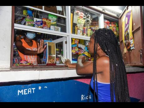 A shopkeeper rejects the cash from a customer at a corner shop on Olympic Way, in Andrew Holness' St Andrew West Central constituency, on Thursday evening. Corner shop operators are divided on the prime minister's criticism of COVID-19 breaches.